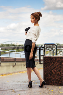 Young fashion business woman with handbag walking on the city street