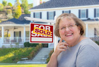 Senior Adult Woman in Front of Real Estate Sign, House