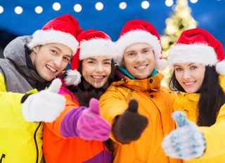 happy friends in santa hats and ski suits outdoors