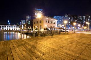 empty wood sidewalk near water in modern city