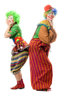 Two smiling clowns are back to back. Isolated