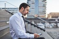 Junger Geschäftsmann nutzt Smartphone App