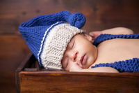 Sweet little newborn sleeps inside a wooden crate