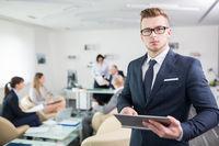 Junger Geschäftsmann mit Brille und Tablet PC