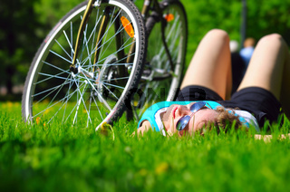 woman is lying near her bicycle