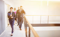 Businesswoman Walking On Corridor With Colleagues By Railing In Office