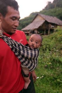 Ein Vater mit seinem Babyt bei Vang Vieng in der Bergregion der Nationalstrasse 13 zwischen Vang Vieng und Luang Prabang in Zentrallaos von Laos in Suedostasien.