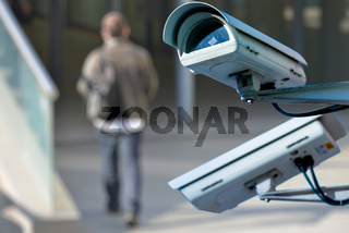 security CCTV camera or surveillance system with man on blurry background