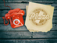 Pizza ordering and delivery concept. Vintage telephone and pizza boxes on wooden background.
