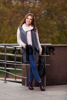 Young fashion woman in grey coat with handbag on city street