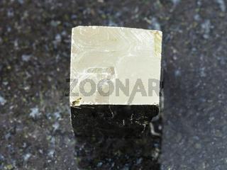 rough pyrite cube on dark background