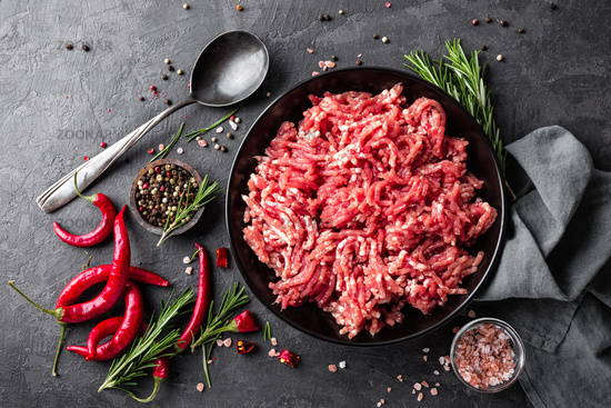 Mince. Ground meat with ingredients for cooking on black background. Top view