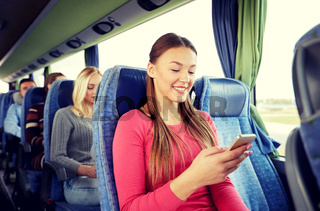 happy woman sitting in travel bus with smartphone