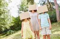 Familie mit Gesichtern unter Pappkartons versteckt
