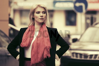 Young fashion business woman walking on city street
