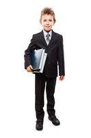 Smiling child boy in business suit holding books