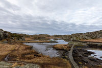 Brown winter landscape with beautiful sky. Pond by the trail, at the Rovaer archipelago, island in Haugesund, Norway.