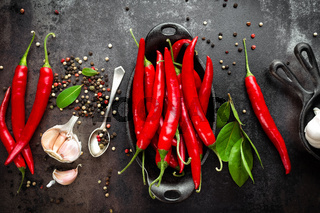 red hot chili pepper corns and pods on dark old metal culinary background