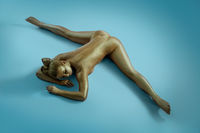 Woman art nude portrait with gold skin shot from above