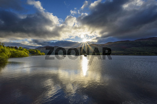 Lake with dramatic clouds and sun in spring