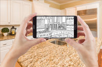 Hands Holding Smart Phone Displaying Drawing of Kitchen Photo Behind