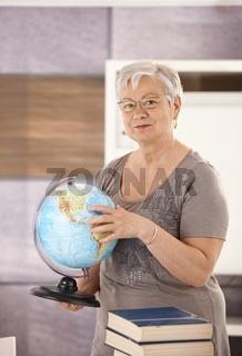 Senior teacher holding globe
