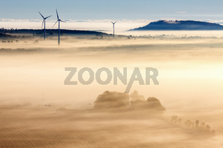 Morning fog over a rural landscape with wind turbines