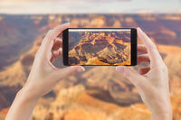 Female Hands Holding Smart Phone Displaying Photo of The Grand Canyon Behind.