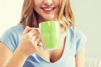 happy woman or teen girl drinking tea from cup