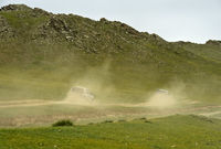 Two four-wheel-drive vehicles with tourists on a dusty dirt road in the Orkhon Valley, Mongolia