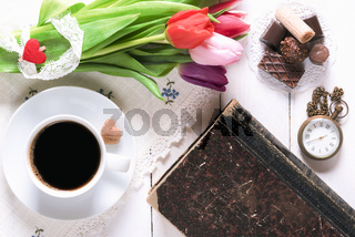 Flowers and old book with coffee and sweets
