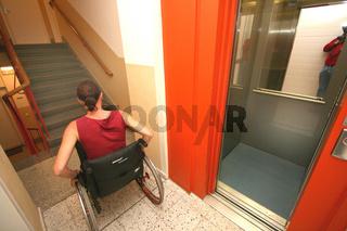 Frau im Rollstuhl in einem Treppenhaus mit Lift im Halbstock