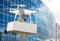 Unmanned Aircraft System (UAS) Quadcopter Drone Carrying Blank Package Near Corporate Building.