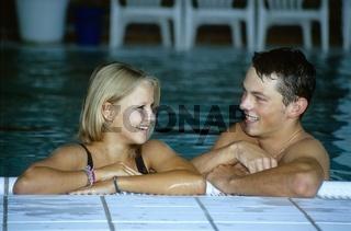 Ein junges Paar genießt das warme wohltuende Wasser im Wellnessbereich