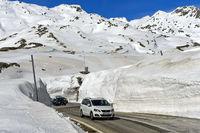 Car driving on the pass road between high snow walls across the St Gotthard Pass,Switzerland