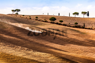 Tuscany fields autumn landscape, Italy. Harvest season, tractor working
