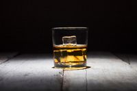 Glass of whiskey with ice cubes served on white wooden planks.