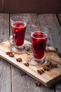 Mulled wine on wooden board and ancient table. Studio shot with mystic light effect