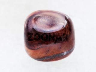 tumbled jaspilite gem stone on white marble
