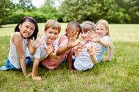 Kinder auf einer Wiese winken fröhlich