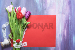 Tulips bouquet with lace on a red paper sheet