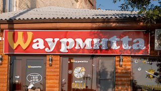 Astrakhan, Russia, May 24, 2016: Local fast food using turned well known M of McDonald's in brand name. McDonald's is the world's largest chain of fast food restaurants. Brand mimicry.