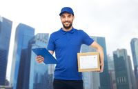happy delivery man with parcel box and clipboard