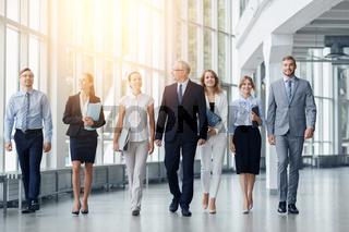 business people walking along office building