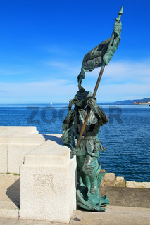 Statue of a soldier with flag at Trieste waterfront, Italy
