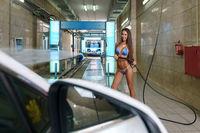 Photo of sexy babe in bikini works at car wash