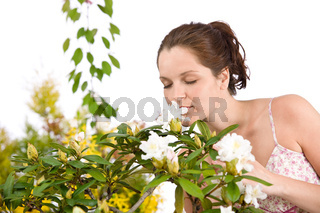 Portrait of woman smelling blossom of Rhododendron flower