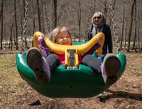 Grandmother and granddaughter play in plastic swing