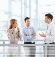 Businesspeople chatting in modern office lobby