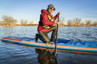 senior male paddler on a stand up paddle board,